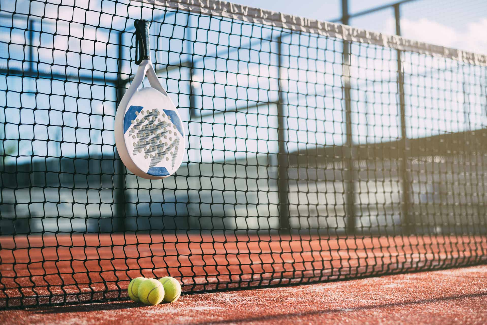 Padel blade racket hanging on the net